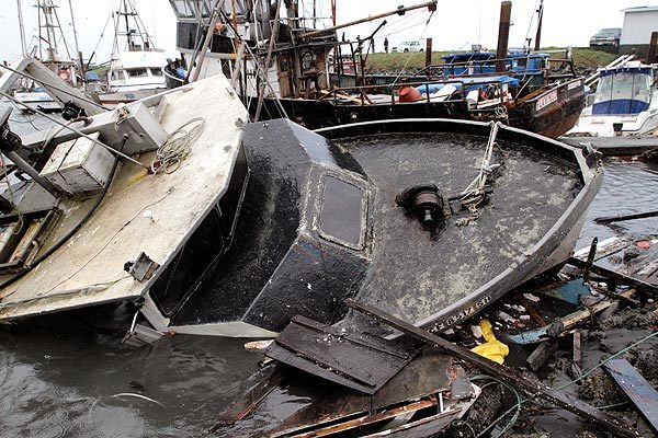 Boats lie half-sunken amid tangled debris and broken docks in Crescent City a day after the tsunami.