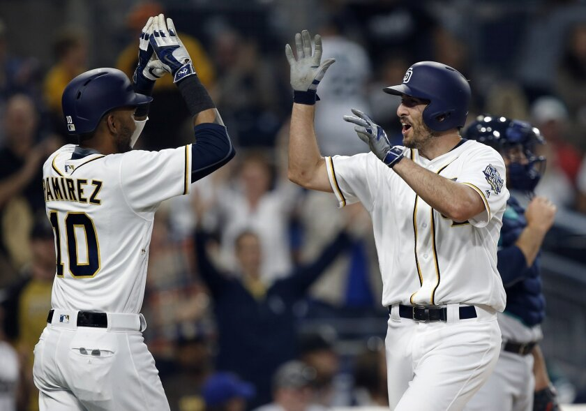 San Diego Padres' Alexei Ramirez, left, congratulates Adam Rosales on the latter's two-run home run against the Seattle Mariners during the first inning of a baseball game in San Diego, Wednesday, June 1, 2016. (AP Photo/Alex Gallardo)