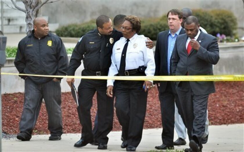 Jackson, Miss. Assistant Chief Lee Vance, center left, comforts Chief Rebecca Coleman, center right, Thursday, April, 4, 2013, after detective Eric Smith was shot and killed inside the Jackson Police Department. A suspect was also killed. (AP Photo/The Clarion-Ledger, Greg Jenson)