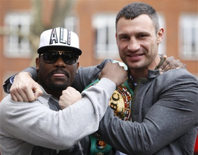 Ukrainian boxer Vitali Klitschko, right, pose for the media with challenger British boxer Dereck Chisora outside a London hotel Monday, Jan. 9, 2012. The WBC World Heavyweight Champion Klitschko will be fight Chisora for the title on Feb. 18, in Munich, Germany. (AP Photo/Alastair Grant)