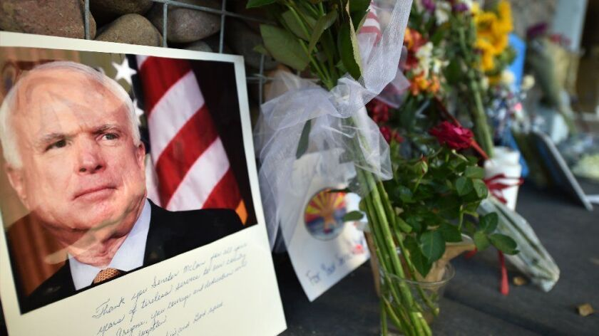 Photographs, flowers and notes gather at a makeshift memorial to John McCain outside his office in Phoenix on Aug. 26.