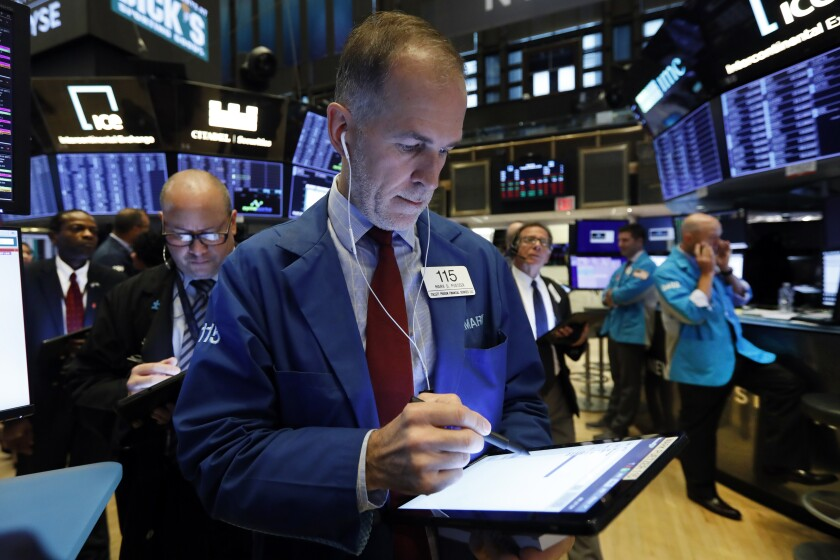 FILE - In this Oct. 8, 2019, file photo trader Mark Puetzer, center, works on the floor of the New York Stock Exchange. The U.S. stock market opens at 9:30 a.m. EDT on Tuesday, Oct. 15. (AP Photo/Richard Drew, File)
