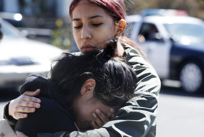 Liana Lopez, the sister of shooting victim Steven Lopez, is comforted by friend Maria Borjas following a press conference Tuesday to announce a $50,000 reward for information that could crack the year-old murder case.