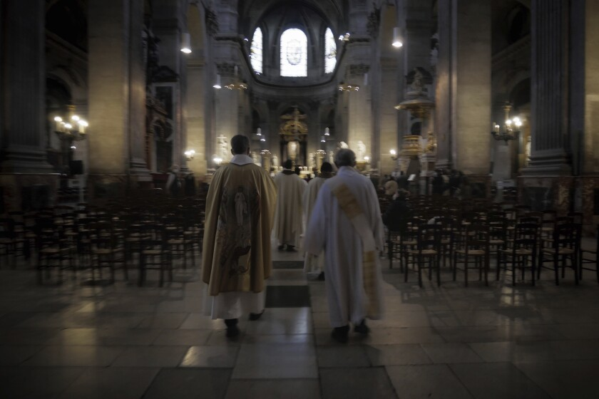 Priest Henri de La Hougue, left, and his assistants celebrate the All Saints Day mass in Saint-Sulpice church, in Paris, Sunday, Nov. 1, 2020. France heightened its security alert amid religious and geopolitical tensions around cartoons mocking the Muslim prophet. (AP Photo/Thibault Camus)