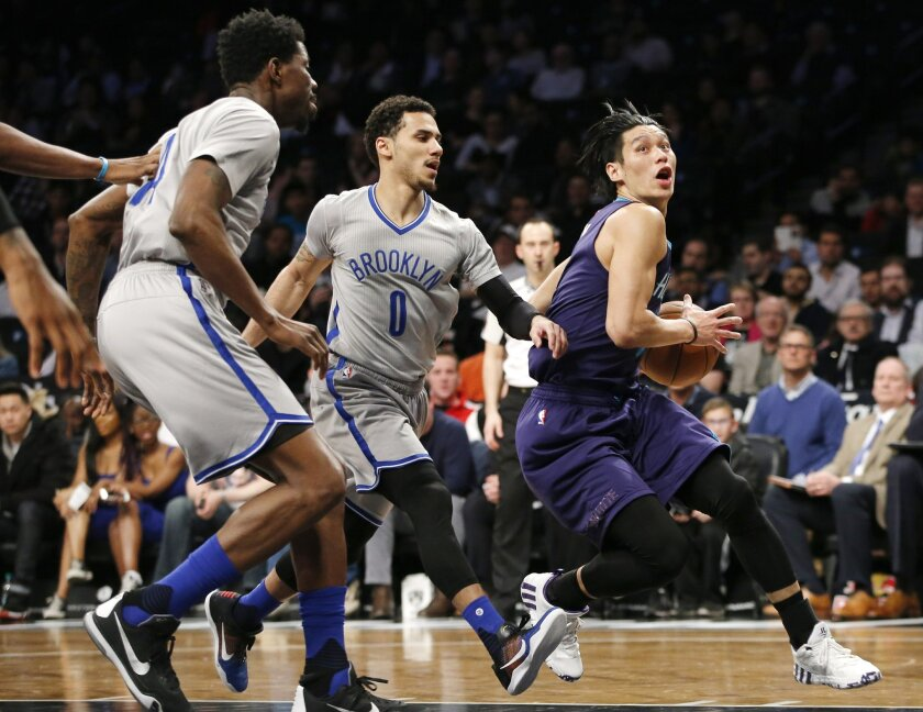 Charlotte Hornets guard Jeremy Lin (7) looks for a shot as Brooklyn Nets forward Thaddeus Young (30) and guard Shane Larkin (0) defend during the first half of an NBA basketball game, Tuesday, March 22, 2016, in New York. (AP Photo/Kathy Willens)