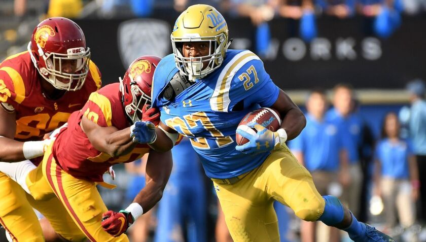 UCLA running Joshua Kelley picks up yards with USC linebacker John Houston (10) pulling at his sleeve during the second quarter Saturday at the Rose Bowl.