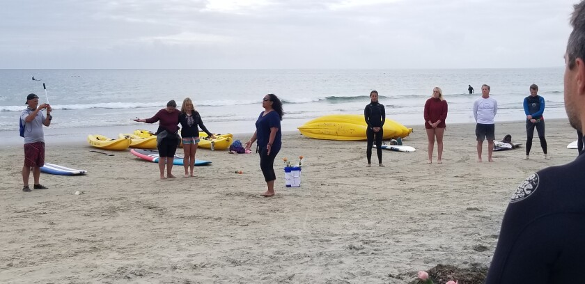 """Kuuipo Kekawa leads paddle-out participants in a """"calling in of the ancestors"""" chant and blessing at La Jolla Shores."""