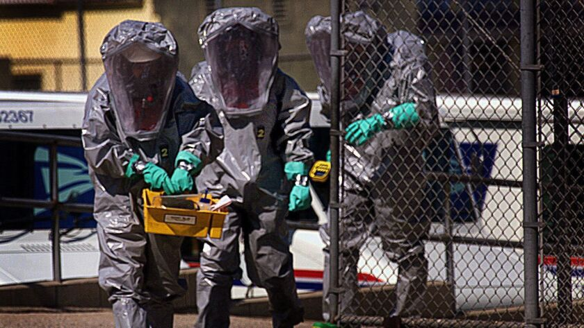 A trio of Los Angeles city firefighters in full Haz Mat suits make their way out of the US Post Offi