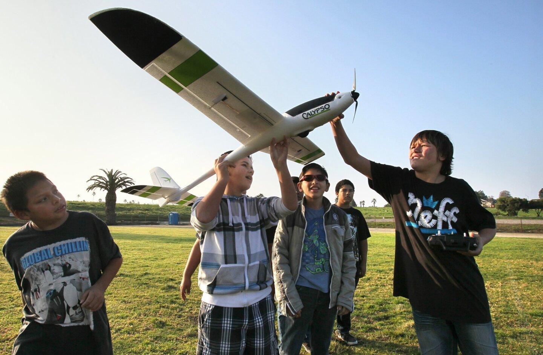 Jefferson Middle School students prepare the remote control plane for a flight, LtoR: Julio Lara, Josh Ramirez, Karim Landeros, Benny Perry (in distance), and James Smith with remote control.