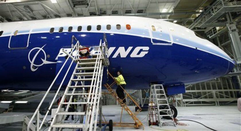 FILE - In this April 30, 2009 file photo, a worker climbs aboard a 787, the first of the model scheduled to fly, at the plant in Everett, Wash. Boeing Co. said late Thursday, Dec. 10, 2009, the long-anticipated first flight of its new 787 jetliner could come as early as Tuesday.(AP Photo/Elaine Thompson, file)