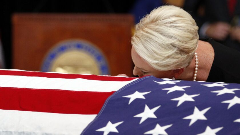 Cindy McCain, wife of, Sen. John McCain, R-Ariz. lays her head on the casket during a memorial servi
