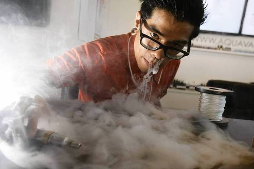 """Aaron Flores exhales water vapor from an electronic cigarette at AquaVape in Temple City. When the user presses a button on the side of the gadget, it heats up the """"juice,"""" which comes in various flavors and levels of nicotine, including none."""