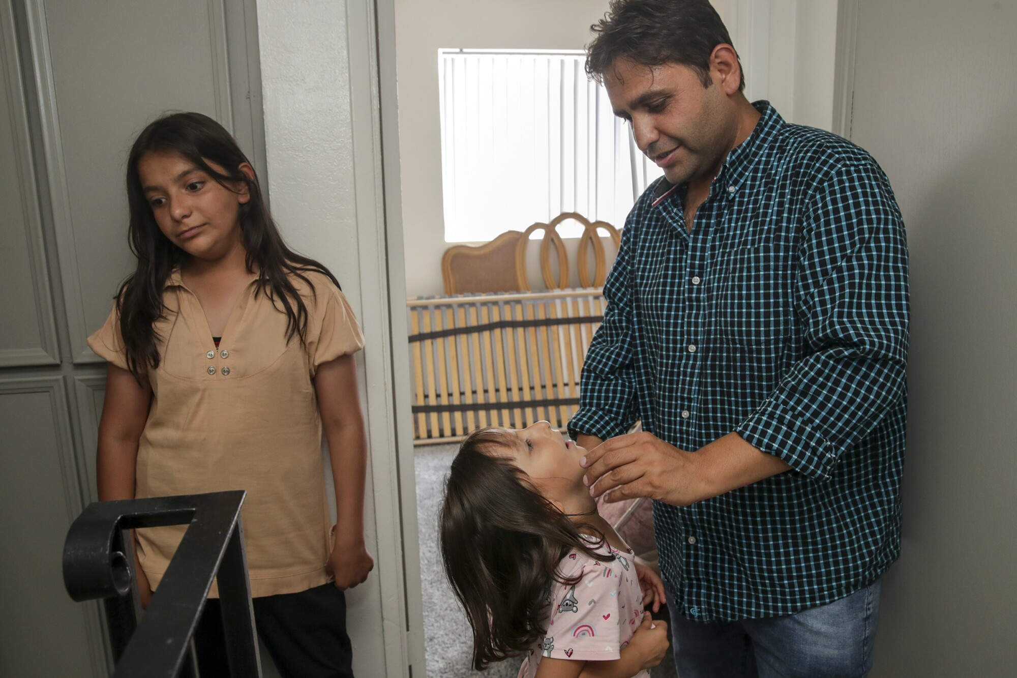 Sayed Omer Sadat, an Afghan refugee, with daughters Asma, 11, left, and Aqsa, 6, in their new apartment in El Cajon.