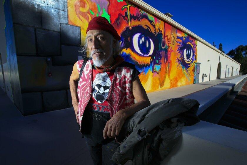 El artista Mario Torero de pie junto a Los Ojos de Picasso en el edificio de artes en San Diego State University.