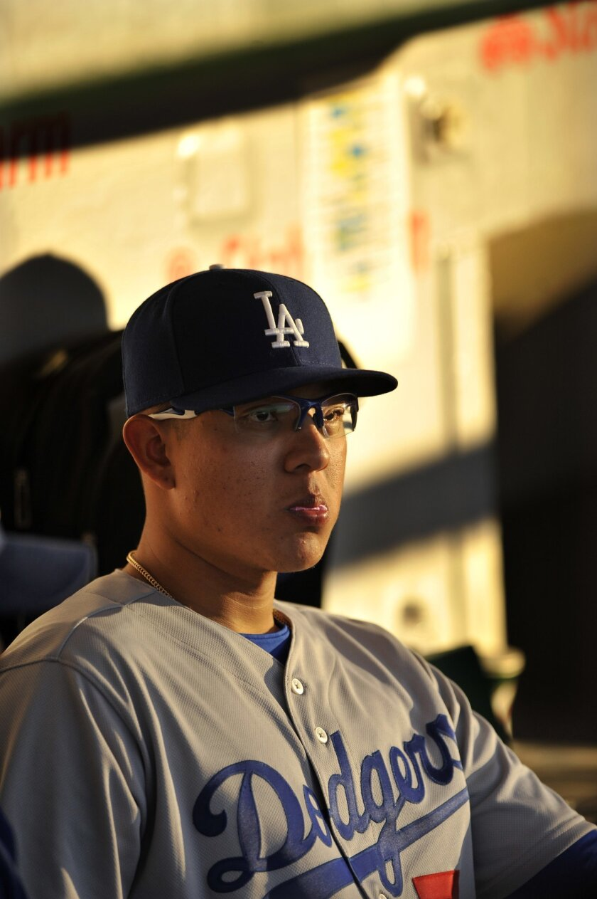 Los Angeles Dodgers pitcher Julio Urias watches from the dugout during the third inning of a baseball game against the Chicago Cubs on Wednesday, June 1, 2016, in Chicago. Chicago won 2-1. (AP Photo/Paul Beaty)