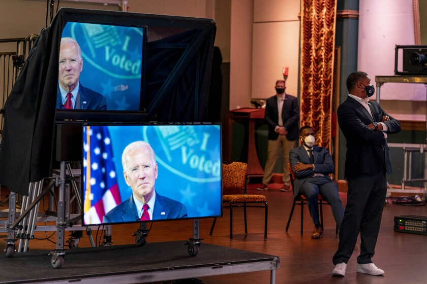 """Rep. Cedric Richmond, D-La., right, watches as Democratic presidential candidate former Vice President Joe Biden appears on a """"Zoom with Oprah Winfrey"""" virtual show at The Queen theater in Wilmington, Del., Wednesday, Oct. 28, 2020. (AP Photo/Andrew Harnik)"""