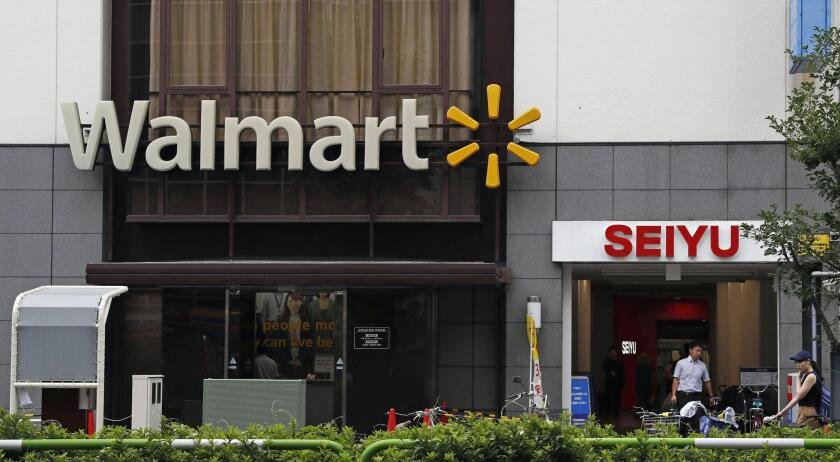 Company signs of Walmart and Seiyu are seen in Tokyo on July 12, 2018. U.S. retailer Walmart is selling off 85% of its wholly owned Japanese supermarket subsidiary Seiyu, while retaining a 15% stake, in a deal valued at ¥172.5 billion ($1.6 billion), the companies said Monday, Nov. 16, 2020.(Kyodo News via AP)
