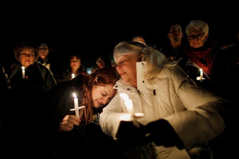 Jeannie Durbin-Hambric, left, leans on Linda Grise, as they join other community members for a vigil at Glenknoll Elementary School.