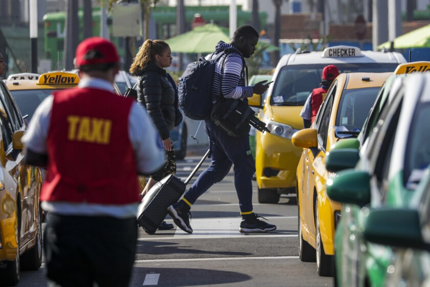 """Passengers arriving at Los Angeles International Airport catch rides with Uber, Lyft and taxi drivers at the airport's new """"LAXit"""" pickup area on Nov. 5."""