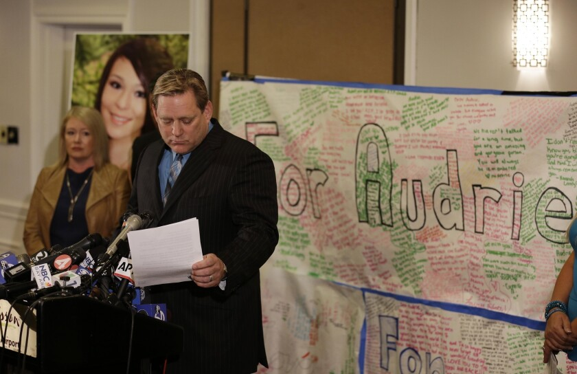 Larry Pott, father of Audrie Pott, who committed suicide after she was sexually assaulted, reads a statement at a news conference in San Jose. Audrie's mother, Sheila Pott, is at left.