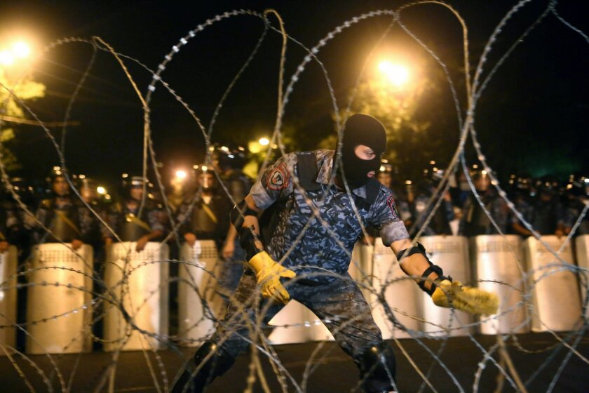 A riot police officer installs barbed wire as others block the street towards the Presidential Residence to prevent a march of anti-government protesters, supporters of the armed group who have been holed inside a police station, in Yerevan, Armenia, Saturday, July 30, 2016. Armed members of an opp
