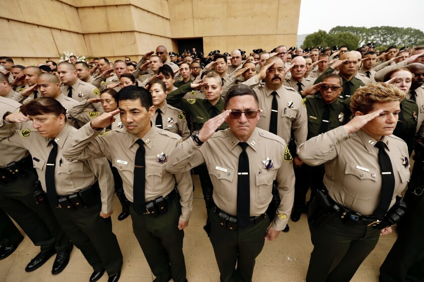 LOS ANGELES CA JUNE 24, 2019 ? Los Angeles County Sheriff's deputies salute during funeral services