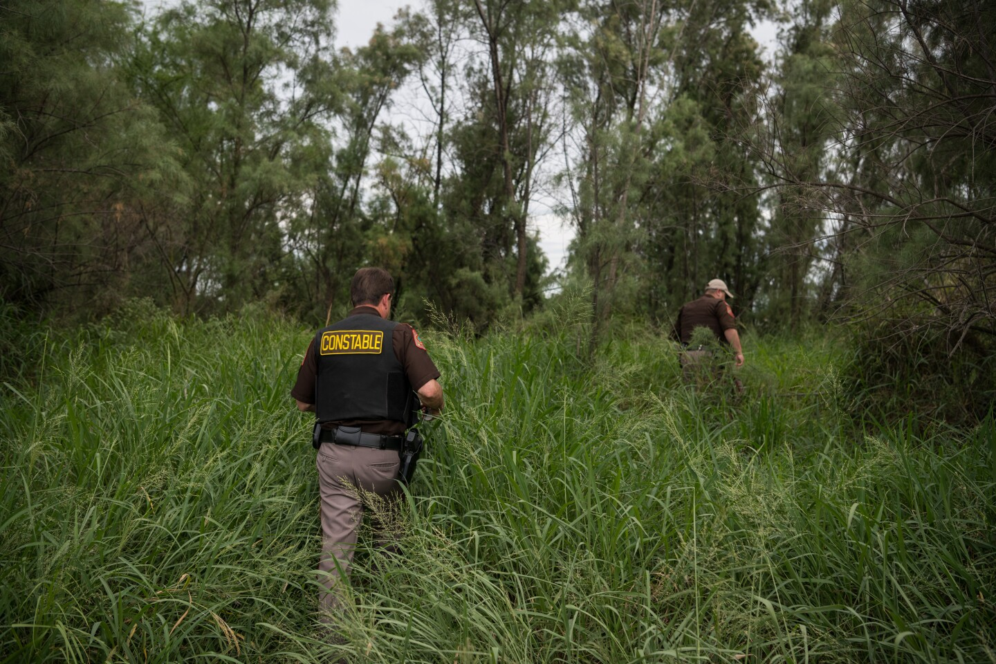 Chief Deputy Rene Gonzalez (L) and Deputy Rey Reyna of the Hidalgo County Constable Precinct 3 Department walk a path to the Rio Grande at a migrant crossing Tuesday, July 23, 2019 near Mission, Texas.