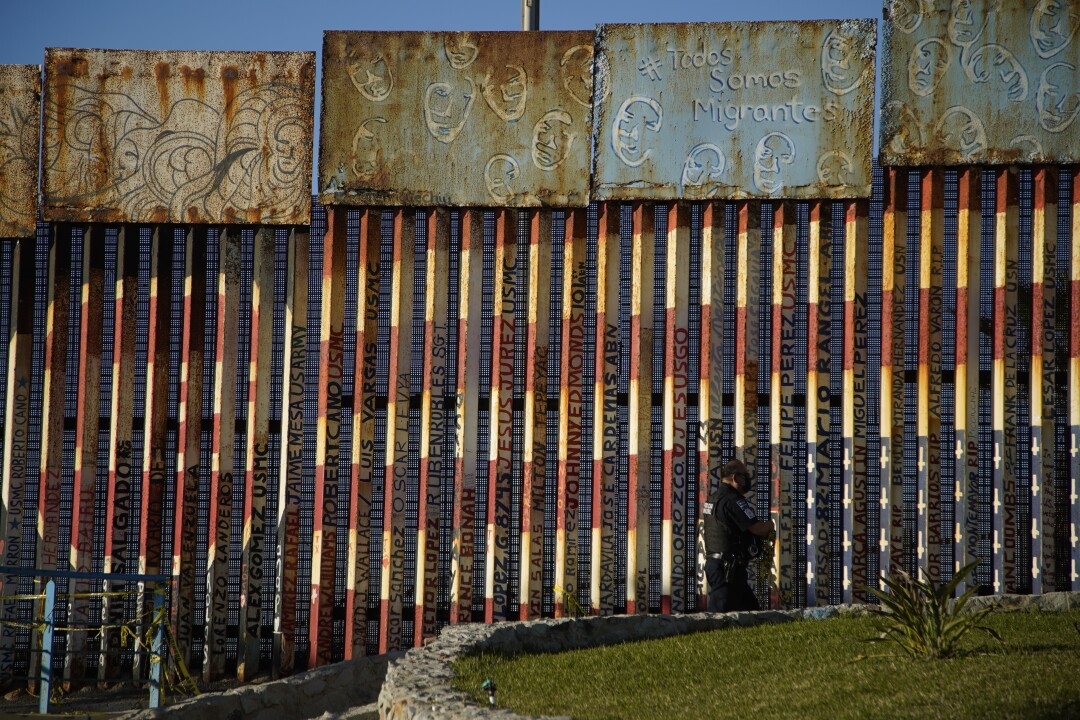 A Mexican police officer patrols near the graffiti-covered border fencing at Playas de Tijuana.