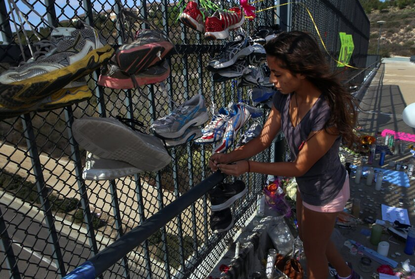 Jazmine Lahbabi, a track team teammate of Steven Liu's at Otay Ranch High, ties a pair of running shoes to a memorial for the boy on a pedestrian bridge near the school. Steven, 17, committed suicide from the bridge.