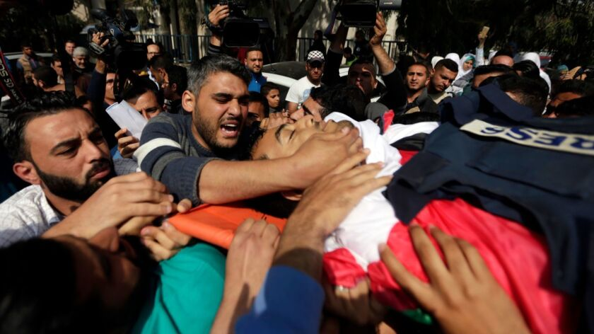 The body of Yasser Murtaja is carried by mourners during his funeral in Gaza City on April 7, 2018. Murtaja was fatally shot during protests at the Gaza-Israel border.