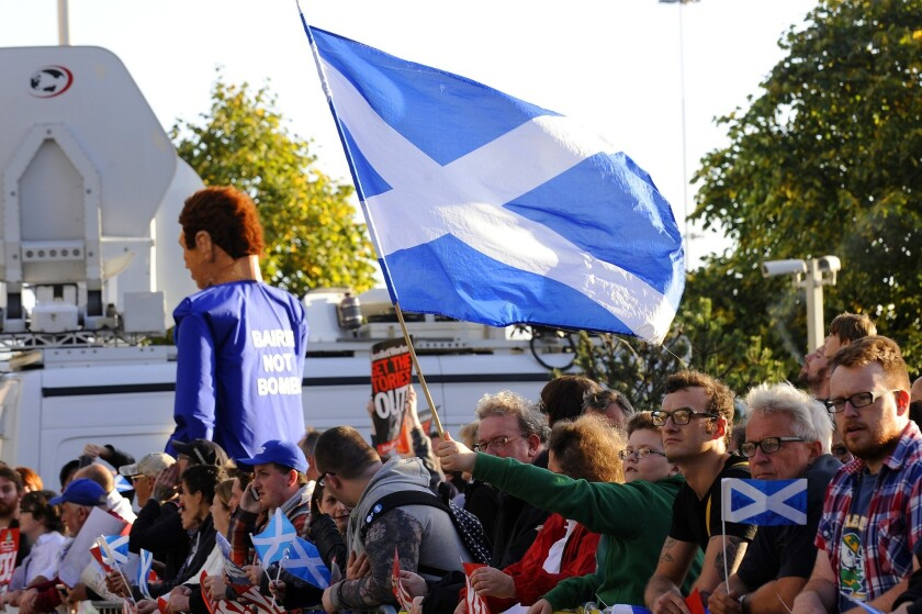 """Protesters in Glasgow hold Scottish Saltire flags outside the venue where British Prime Minister David Cameron addressed the Confederation of British Industry Scotland on Aug. 28, saying that the union between Scotland and England was the """"greatest merger in history."""""""