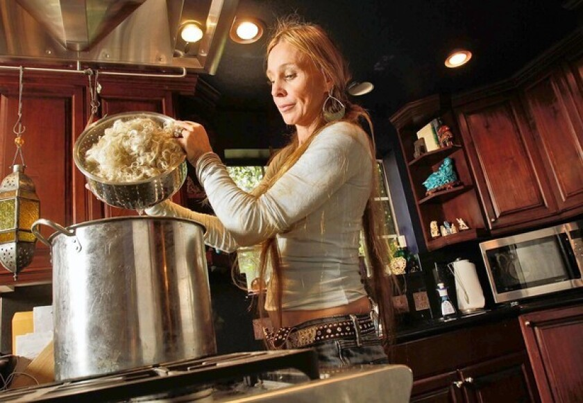 Natalie Redding transfers washed wool into a pot to dye. Her Namaste Farms yarns are more expensive than some but are selling well.