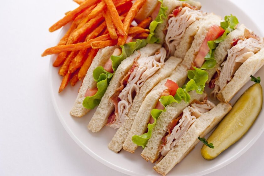 Broken Yoke Cafe's Club Sandwich can be served with fries and a pickle.
