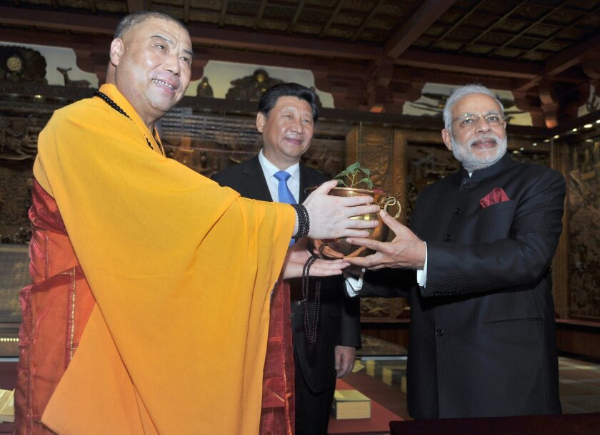 Chinese President Xi Jinping, center, and Indian Prime Minister Narendra Modi, right, hand over a Bodhi tree sapling at an event in China in May. Both leaders are in the U.S. this week to encourage U.S. companies to invest in their countries.