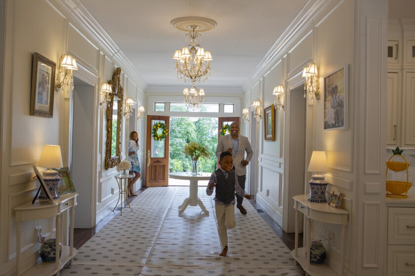 A young boy runs through the hallway of a grand home, with his parents smiling behind him.