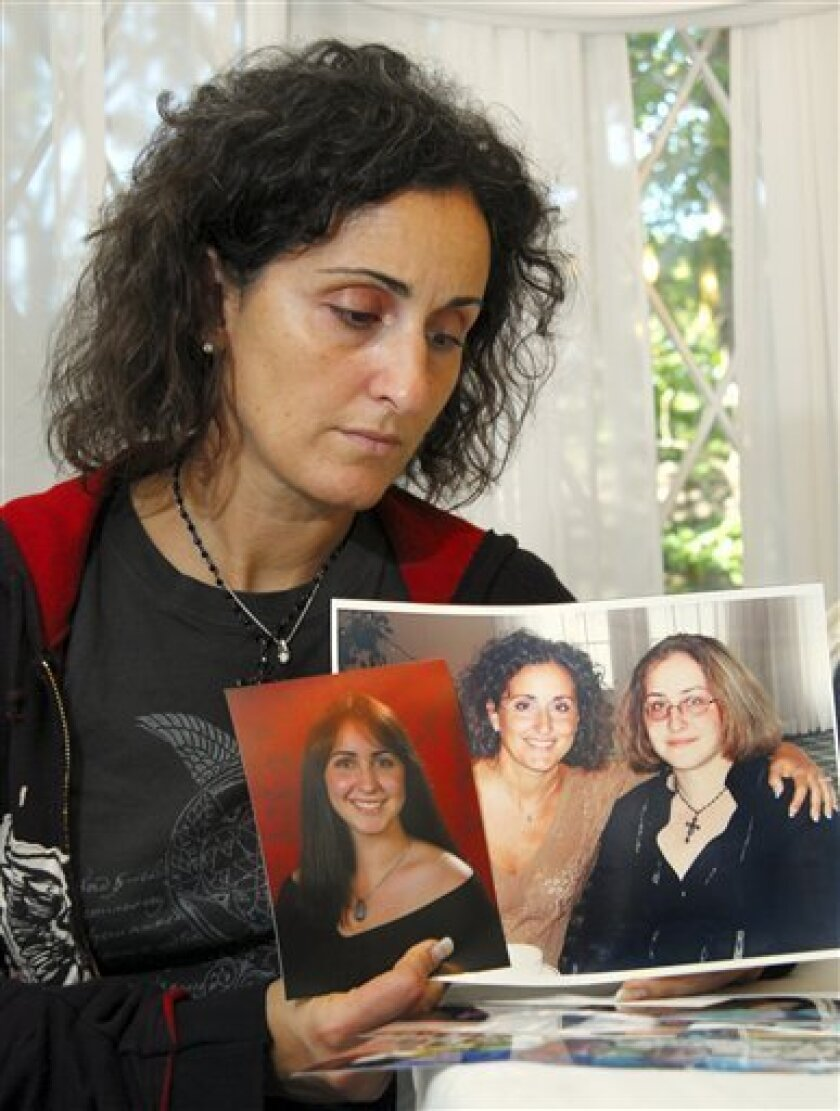 FILE - In this Monday, Oct. 9, 2006 file photograph, Maria Caiafa, of Marmora, N.J., holds photos of her late daughters Christina, 19, in the photo at left, and Jacqueline Becker, 17, at right in the other photo, in Upper Township, N.J. The sisters were killed after New Jersey state trooper Robert Higbee ran a stop sign and collided with their vehicle while on patrol in Cape May County, N.J., September 27, 2006. Two and a half years later, what happened that night will be scrutinized in a New Jersey courtroom this week, where a jury will decide whether Higbee should go to jail for 5 to 10 years, or whether he was just doing his duty, chasing a speeder, when a tragic accident occurred. (AP Photo/Mary Godleski,file)
