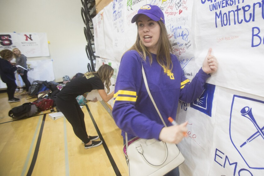 Huntington Beach High School's Devon Kelly signs a banner on behalf of a friend who couldn't attend the college commitment ceremony April 29.