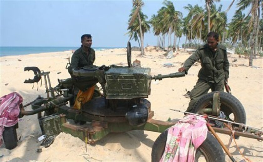 In this Sunday, May 10, 2009 handout photo made available by the Sri Lankan army, soldiers check a weapon used by the Tamil Tiger rebels against security forces in the war zone, in Mullivaaykaal, Sri Lanka. (AP Photo/Sri Lankan army, HO)