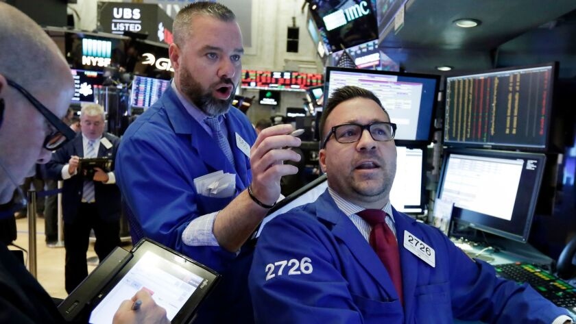 Trader Kevin Lodewick and specialist Paul Cosentino work on the floor of the New York Stock Exchange.