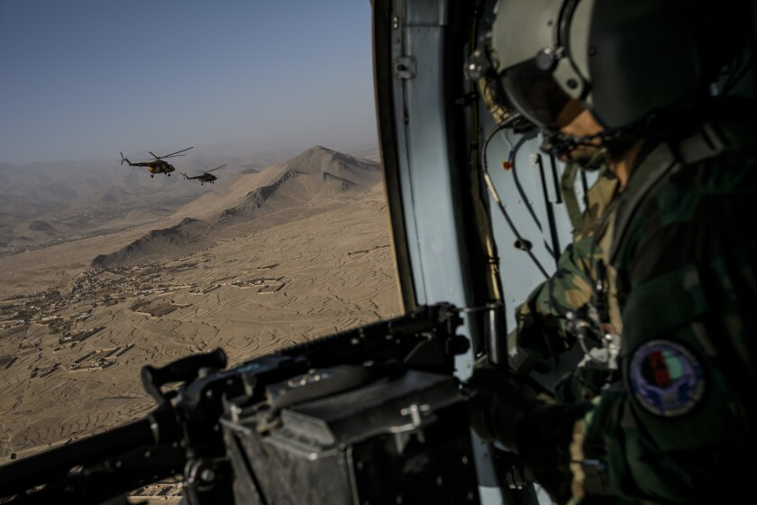 Lt. Obaidullah Haber, member of the 777 Special Mission Wing looks out from a Mi-17 helicopter during a training mission around Kabul, Afghanistan.