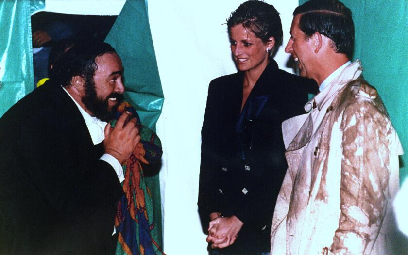 Opera superstar Luciano Pavarotti greets Princess Diana and Prince Charles after his rain-soaked 1991 concert in London's Hyde Park.
