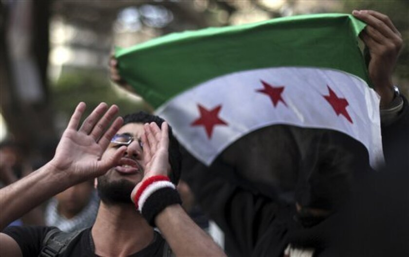 FILE - In this Wednesday, Feb. 6, 2013, file photo, Egyptian and Syrian protesters, with a Syrian revolutionary flag, protest against Iran's President Mahmoud Ahmadinejad during his visit to Egypt for the 12th summit of the Organization of Islamic Cooperation at the Iranian diplomatic representation office in Cairo, Egypt. Once welcomed with open arms in Egypt, Syrians have increasingly found themselves the targets of hate speech and intimidation in the country since the military's ouster of Pre