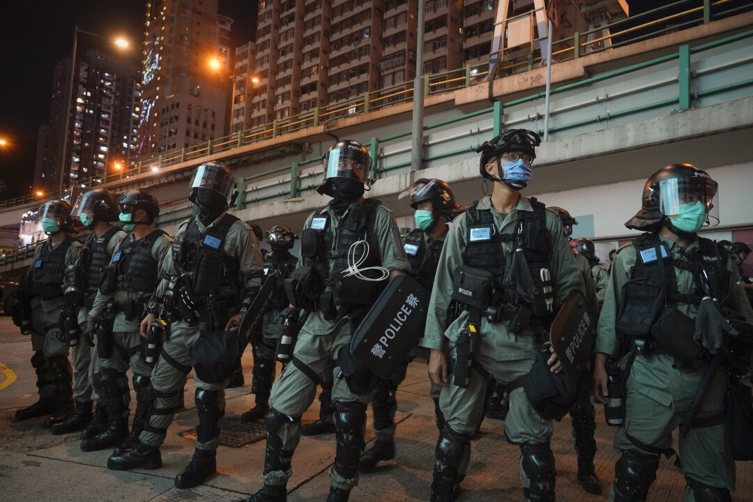 Riot police stand guard after pushing back protesters demonstrating against the new security law