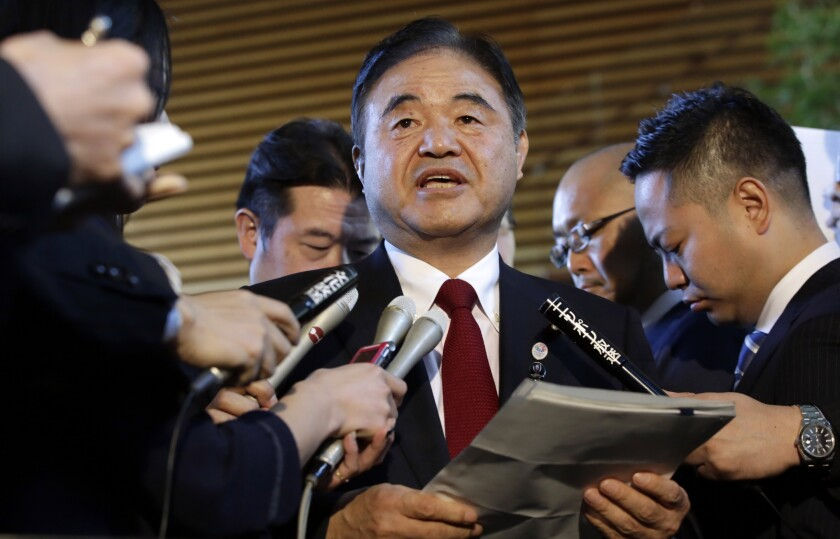 FILE - In this Dec 22, 2015, file photo, Toshiaki Endo, center, minister in charge of the 2020 Tokyo Olympics, speaks with media after a meeting of Cabinet ministers including Japan's Prime Minister Shinzo Abe, at Abe's official residence in Tokyo. Former Olympic minister Endo said at a meeting of the ruling Liberal Democratic Party on Friday, June 5, 2020, that a decision of whether to hold the Games should be made around March, which is a crucial time to finalize participating athletes, NHK said. (AP Photo/Eugene Hoshiko, File)