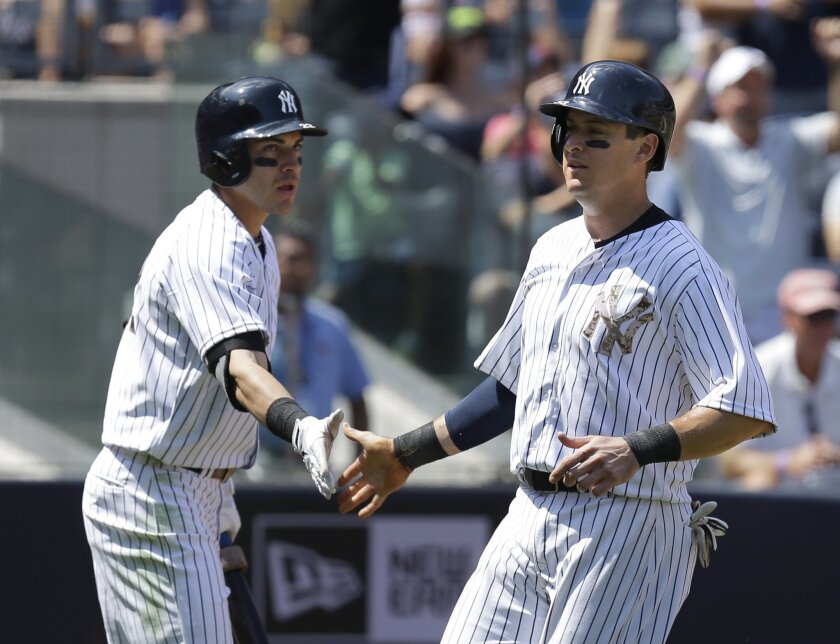 New York Yankees' Kelly Johnson, right, celebrates with Jacoby Ellsbury after scoring during the fifth inning of a baseball game against the Cincinnati Reds at Yankee Stadium on Sunday, July 20, 2014, in New York. (AP Photo/Seth Wenig)