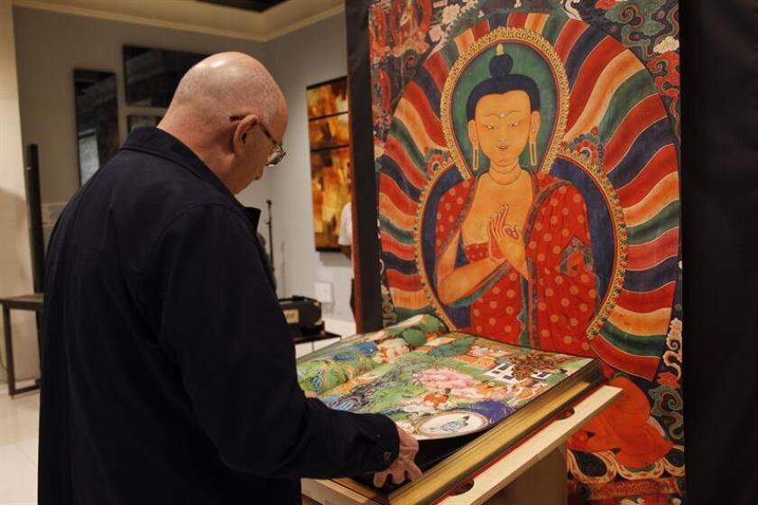 Un hombre observa hoy, miércoles 27 de septiembre de 2018, un libro sobre murales del Tibet de la editorial Taschen, durante su presentación en Ciudad de México (México). EFE