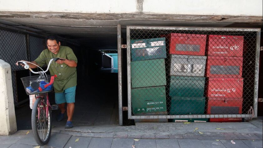 A Thai pedestrian pushes his bicycle next to used ballot boxes in storage outside a district office Jan. 23 in Bangkok.
