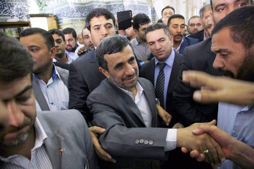 Former Iranian president Mahmoud Ahmadinejad, center, shakes hands during a 2013 visit to Najaf, Iraq.