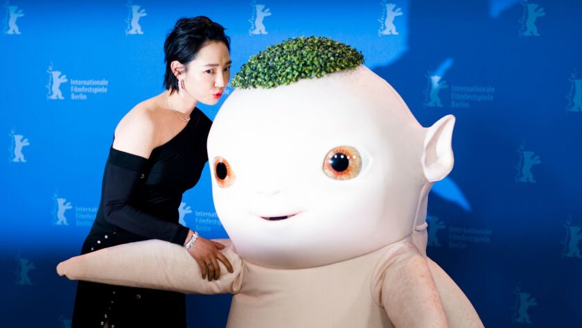 Actress Baihe Bai, left, kisses a person dressed as the character Wuba in the film 'Monster Hunt 2'