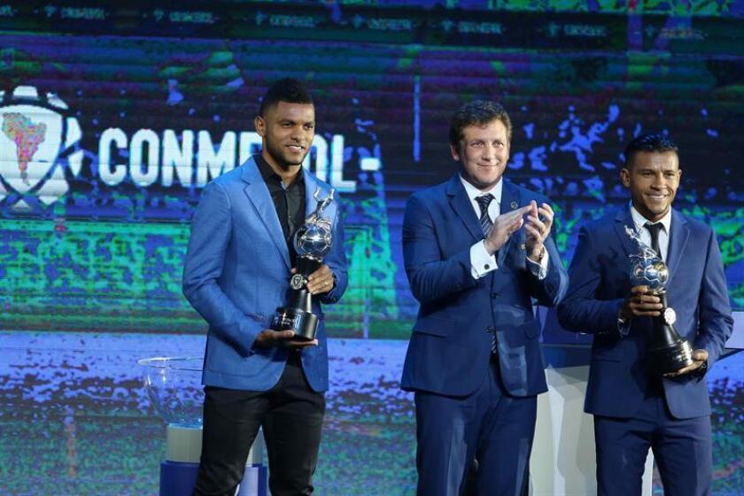 El presidente de la Confederación Sudamericana de Fútbol (Conmebol), Alejandro Domíguez (c), posa hoy con los delanteros colombianos Miguel Borja (izq) y Wilson Morelo (dcha) tras consagrarse como máximos goleadores en la pasada Copa Libertadores, durante el sorteo de las copas Libertadores y Sudamericana de 2019 celebrado en el Centro de Convenciones de la Conmebol en Luque (Paraguay). EFE